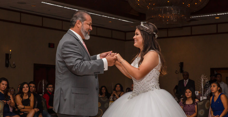 A girl dancing with her father at her Quinceanera